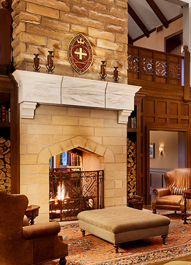 Lobby area with wooden walls and brown leather chairs next to fireplace