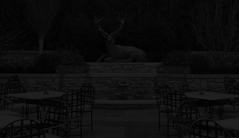 Outdoor terrace seating next to deer statue