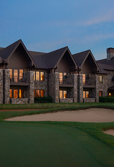 Brick buildings lit up at night next to golf course