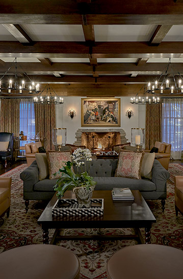 Lobby area with couches, fireplace and multiple candle chandeliers