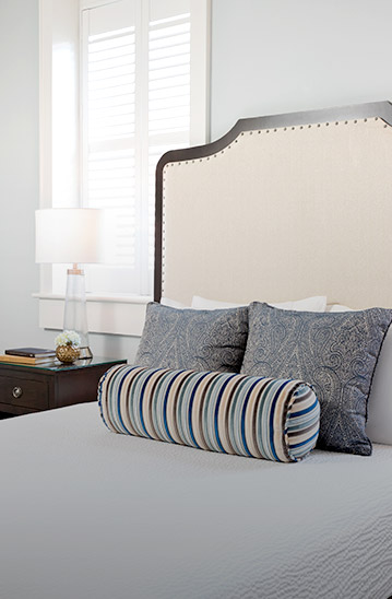 Bed with headboard and patterned throw pillows