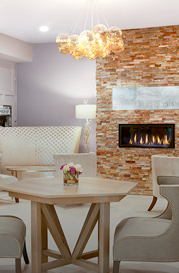 Wooden table with beige chairs next to fireplace