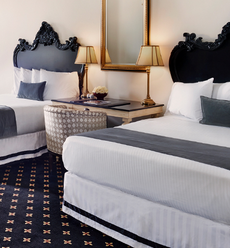 two beds with white linens, gray blanket and throw pillows, and a gray and black ornate headboard
