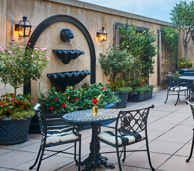 courtyard with black patio furniture and cushioned seats with a fountain and greenery on the walls