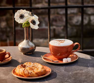 Table with flowers, coffee and pastry