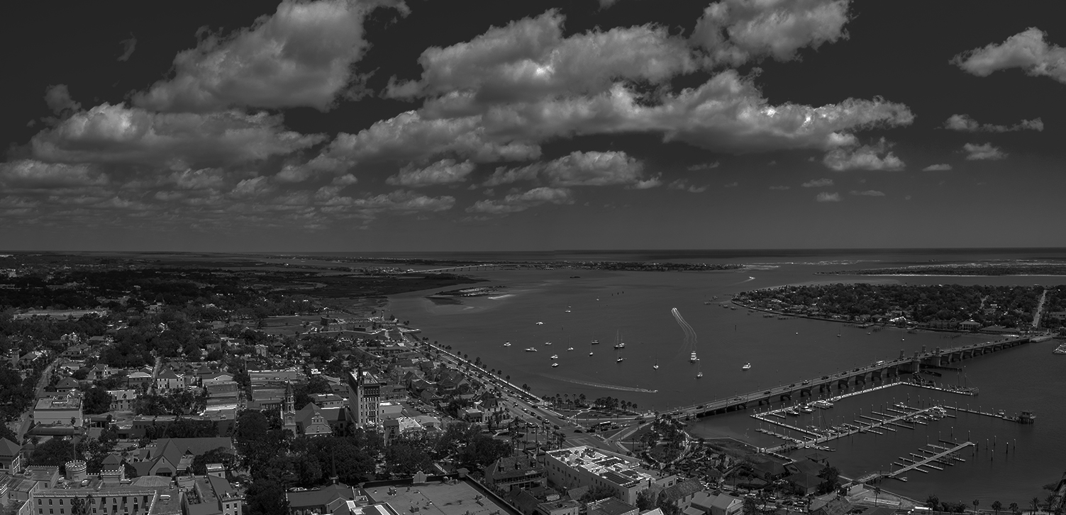 black and white image of an aerial shot of a city on the coast with boats in the ocean