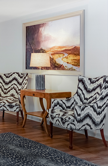 black and white patterned chairs with a brown side table in between them with a lamp and painting on the wall
