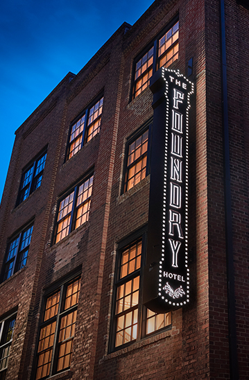 the foundry hotel logo sign lit up at night alongside the brick building