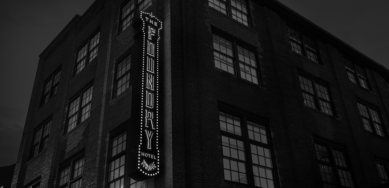 black and white image of the foundry sign lit up outside the hotel