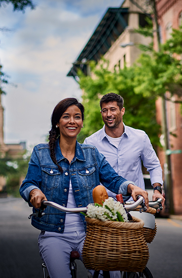 Woman riding bike with man walking behind