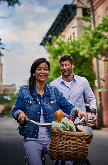 Woman riding bike with man walking behind