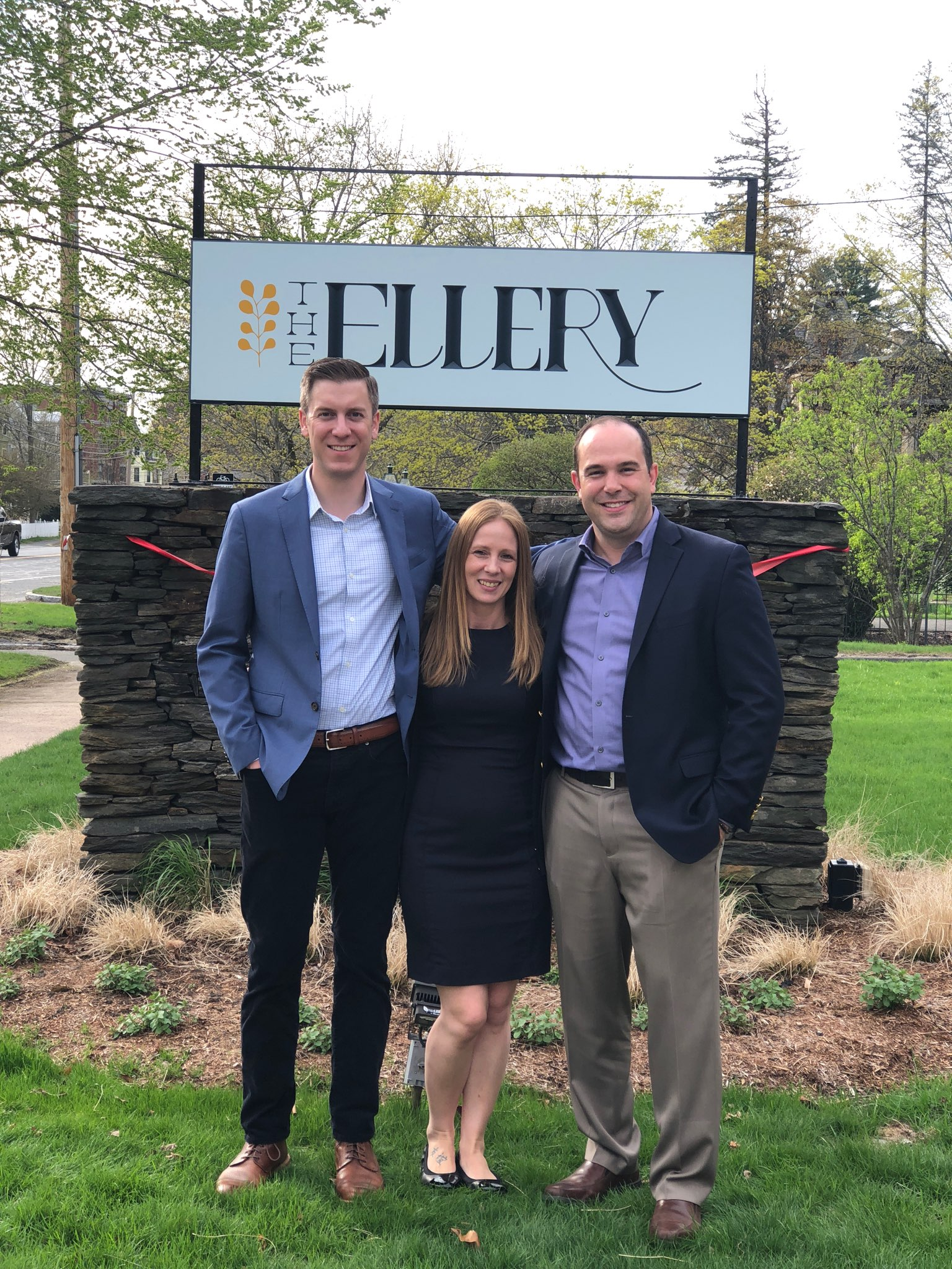 Staff members in front of the ellery hotel sign