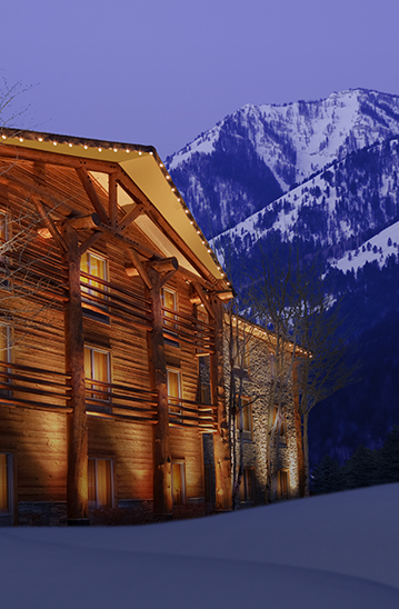 wood exterior building lit up at night with snow on the grounds and mountains