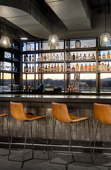 modern bar with neatly organized shelves, light brown bar chairs, and industrial metals