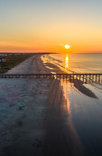 view of an ocean pier as the sun sets in the distance