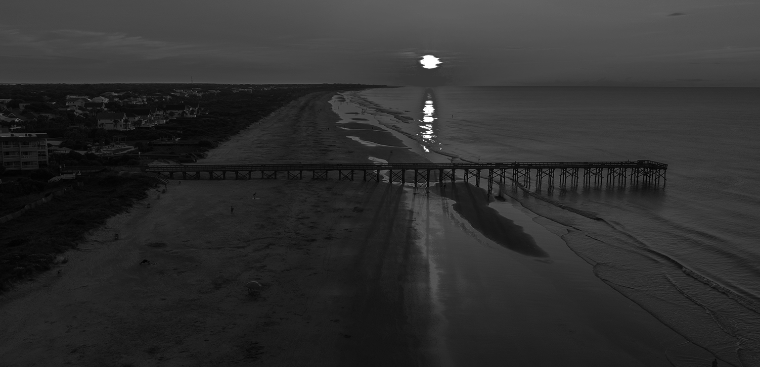 black and white image of a pier with the moon in the distance