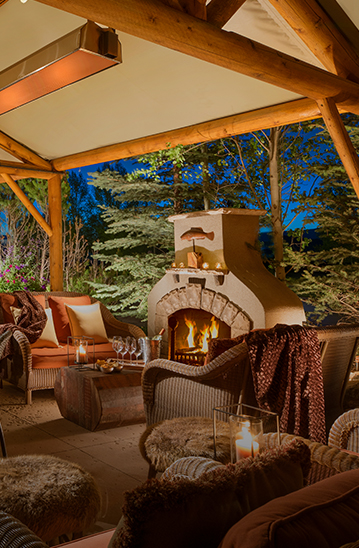 cozy covered patio with a fireplace, comfortable seating, and candles in lanterns next to the chairs