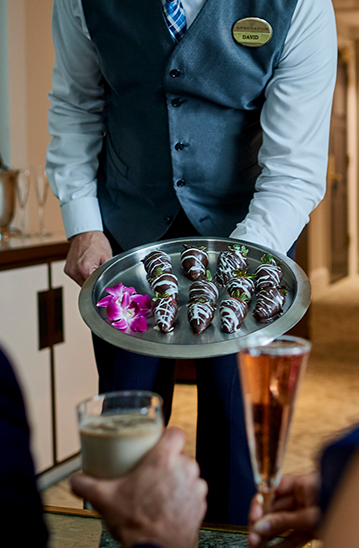 waiter bringing a tray of chocolate covered strawberries to a couple