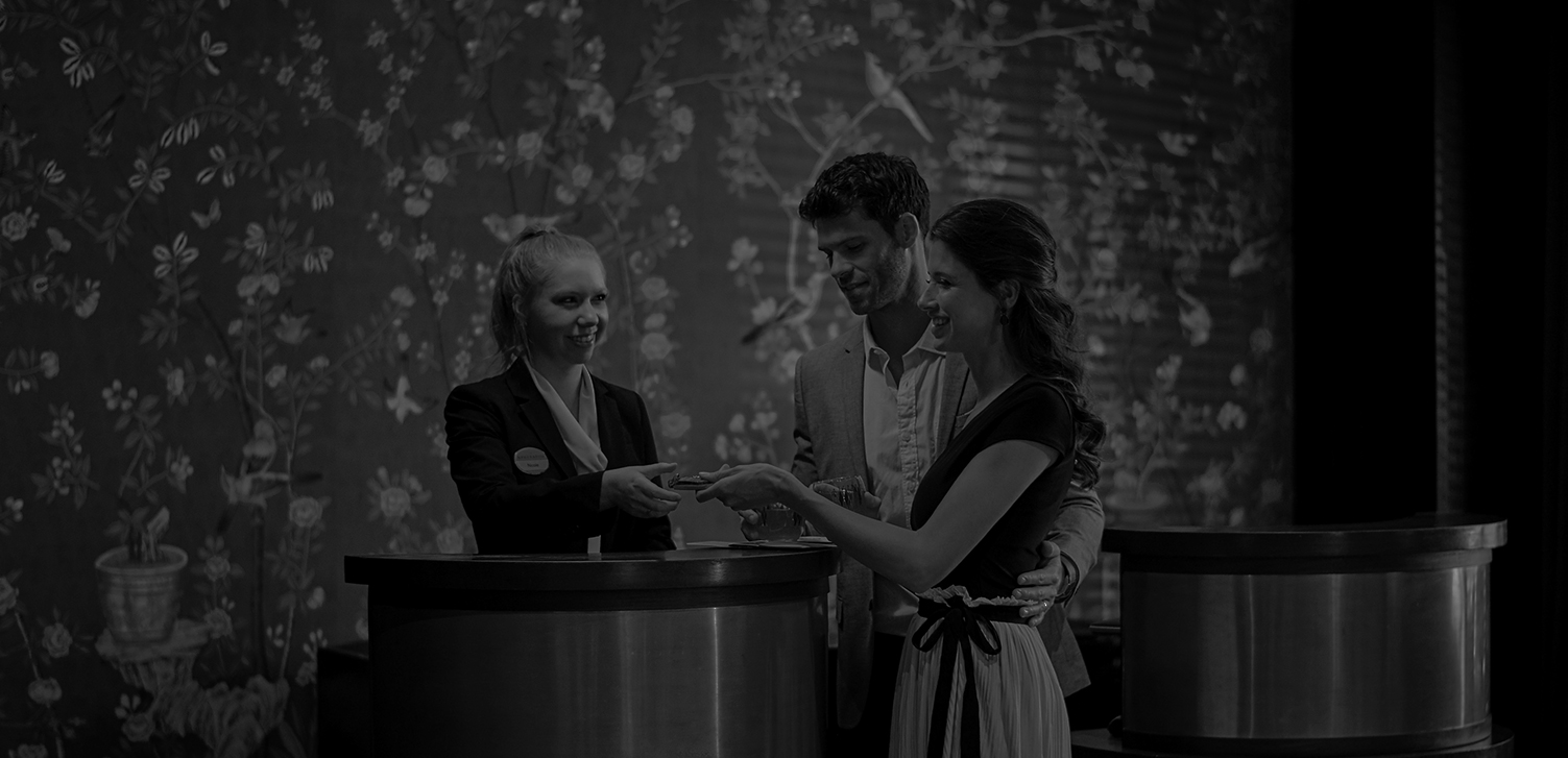 black and white image of a couple checking into a hotel with a front desk attendant