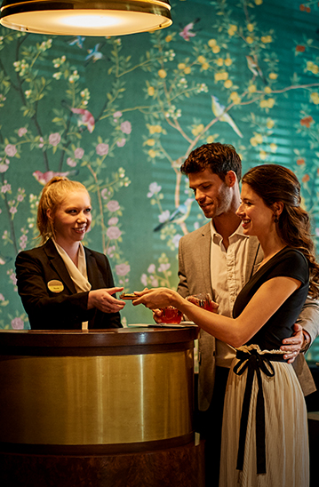man and woman checking into their hotel with a front desk worker