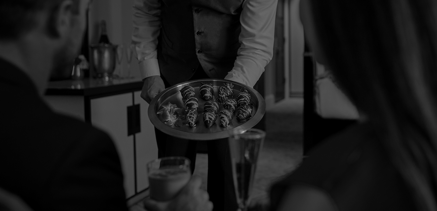 black and white image of a waiter bringing a tray of chocolate covered strawberries to a couples