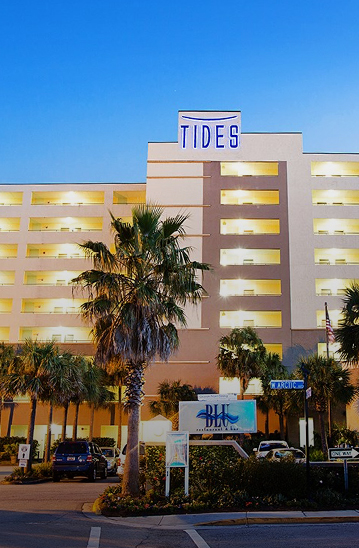 exterior of the tides hotel with outdoor hallways lit up at night and palm trees in front of the building