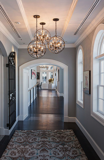 hallway with gray walls, a rug, arched windows on the wall