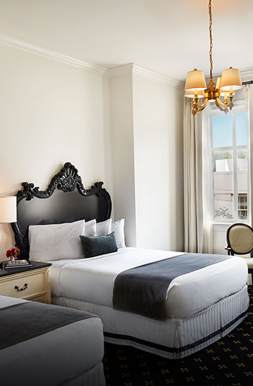 a white hotel room with a black bed