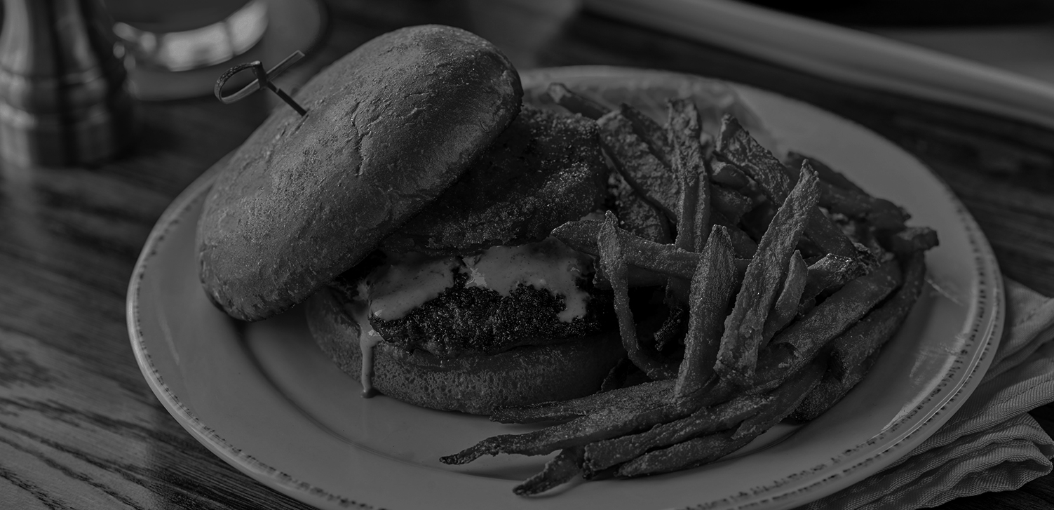black and white image of a burger plate with fries
