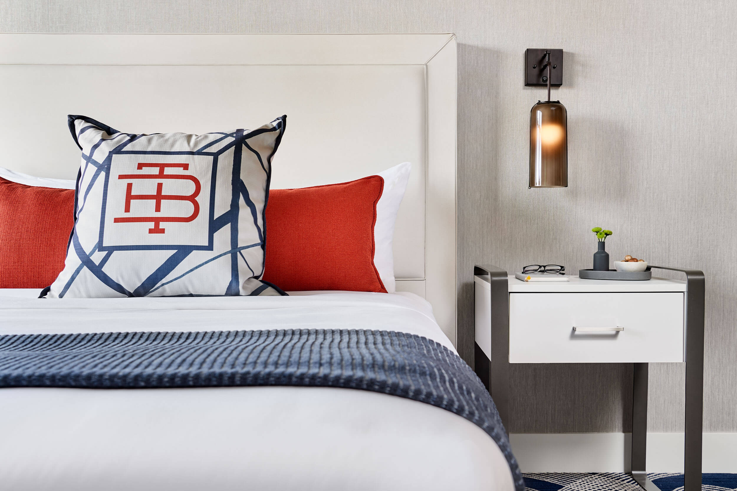 a modern hotel room with blue and red furnishings