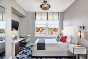 a modern hotel room with gray and blue furnishings
