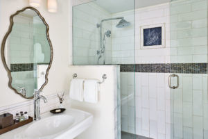 a white bathroom with marble tile and white sink