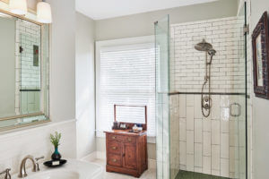 a bathroom with white tile and wood vanity