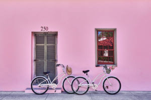 two bikes against a pink wall