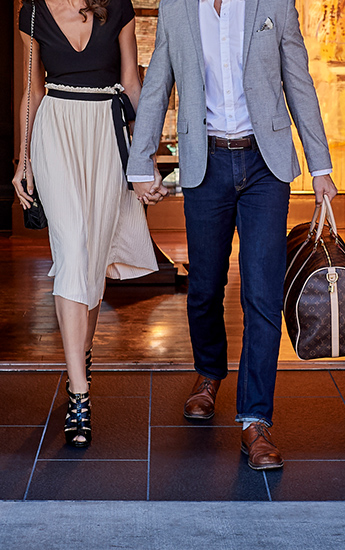 well dressed man and woman holding hands walking out of a hotel lobby with a man holding a carry on bag