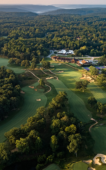aerial view of a golf course surrounded by trees with a building in the distance
