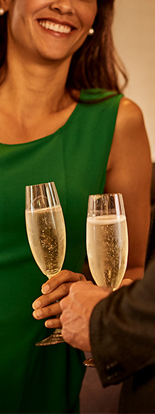 close up of two people holding champagne glasses