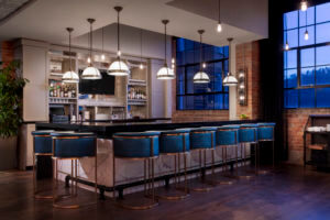 a modern bar with blue leather barstools