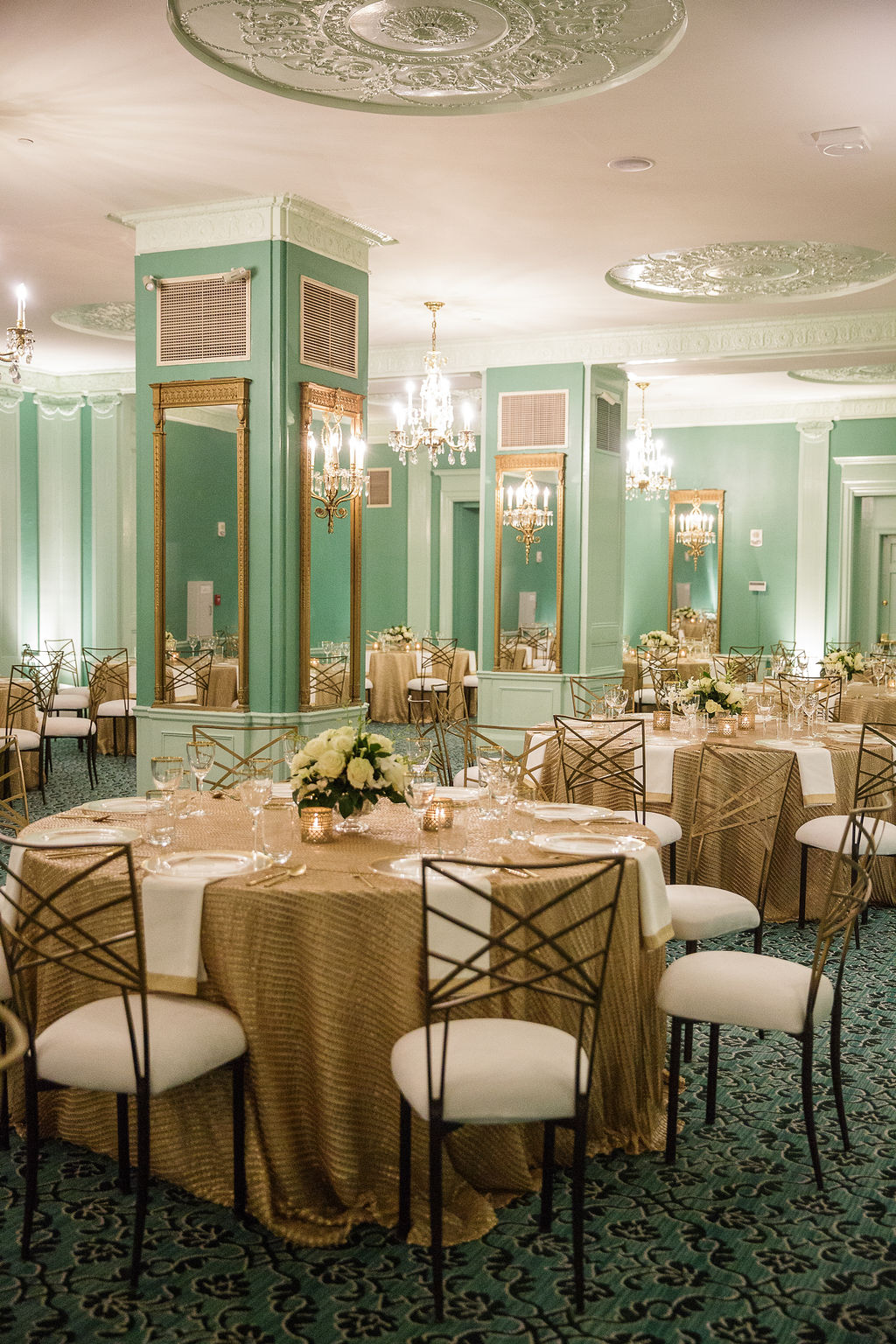 light green elegant dining rooms with mirrors on each column, patterned floor, and tables decorated with gold tablecloths