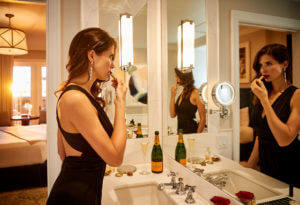 a woman putting on lipstick in front of a mirror