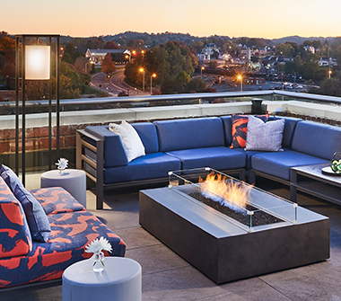 rooftop terrace with a blue couch, blue and red patterned love seat, and modern fireplace in the center of a coffee table