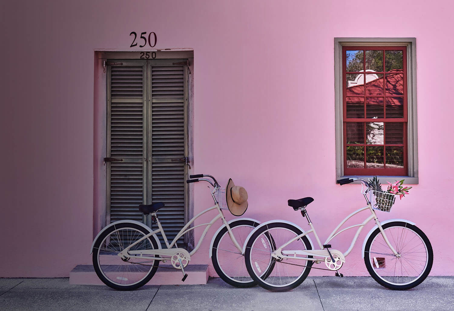 two white bikes parked outside a bright pink building