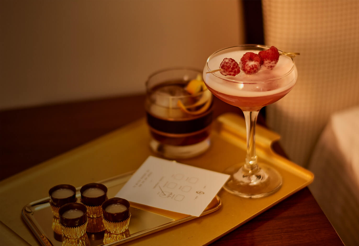 a raspberry cocktail and whiskey drink on a gold tray with small treats and a card